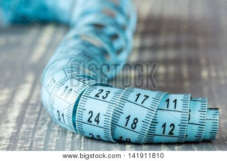 Blue ruler laying on grey wooden background