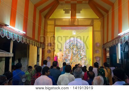 KOLKATA INDIA - OCTOBER 18 2015 : Priest praying to Goddess Durga shot at colored light. It is the biggest religious festival of Hinduism and Bengali Community. Documentary editorial.