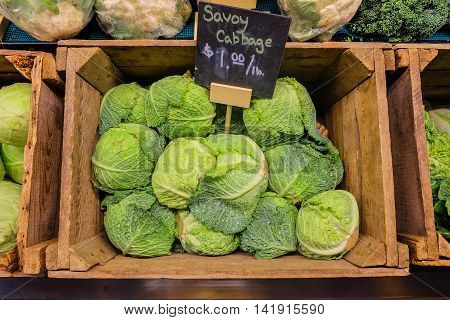 Fresh cabbage vegetable in wooden box stall in greengrocery with price chalkboard label.