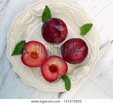 A plate with plums and mint abd basil leaves