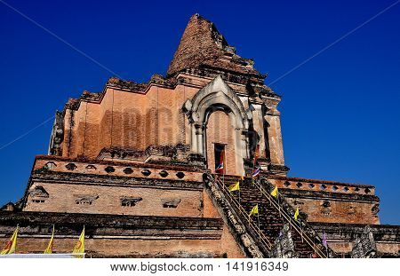 Chiang Mai Thailand - December 19 2012: 1401 Chedi damaged in a 1545 earthquake decorated with elephants on its upper terrace and ornamental niches containing statues of Buddha at Wat Chedi Luang