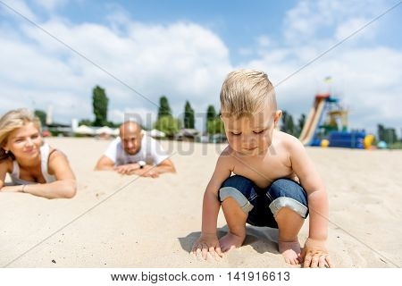 Young family with a toddler resting on the beach. Happy kid playing with his father and mother on the beach in summer.