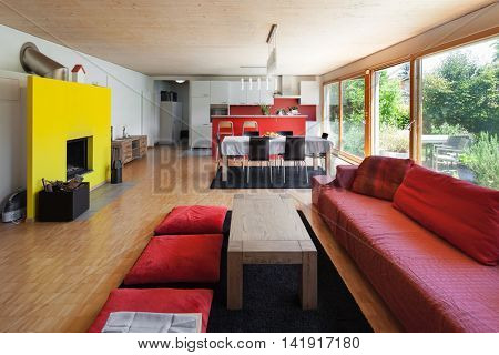Living room of an eco house, red divan