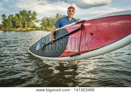 senior male with hist stand up paddleboard on a lake in Colorado