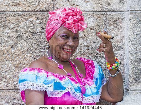 HAVANA CUBA - JULY 18 : A portrait of a Cuban woman smoking cigar in old Havana street on July 18 2016. Cuba now exports more than 90 million cigars a year