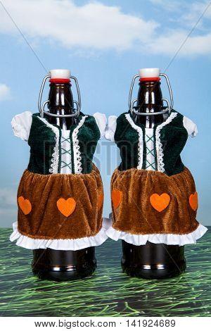 Two beer bottles in Bavarian dirndl dresses