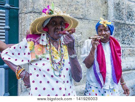 HAVANA CUBA - JULY 18 : A portrait of a Cuban women smoking cigar in old Havana street on July 18 2016. Cuba now exports more than 90 million cigars a year