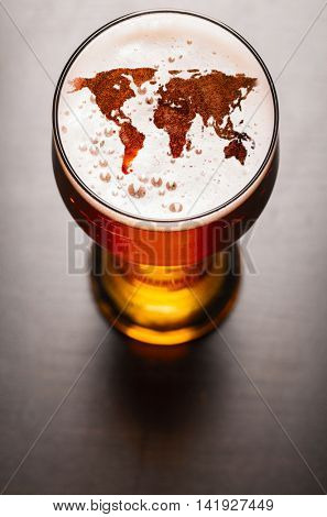 world map silhouette on foam in beer glass on black table. Elements of this image furnished by NASA