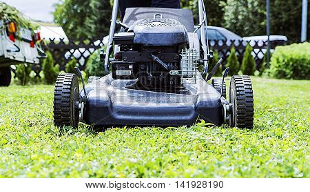 lawnmower closeup, mowing the lawn in the garden of the house