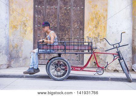 HAVANA CUBA - JULY 18 : A Cuban rickshaw driver in old Havana street on July 18 2016. Rickshaw are a popular way of transport in Cuba
