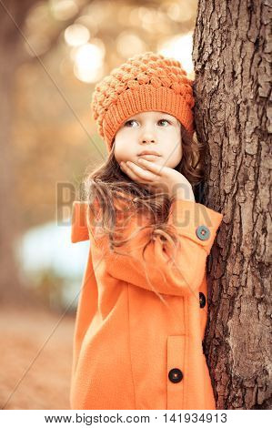 Stylish baby girl 3-4 year old wearing trendy winter jacket and knitted hat outdoors. Looking away. Childhood.