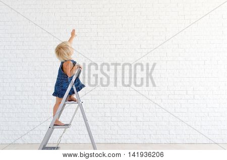 Little girl at the ladder, with the white brick wall on background.
