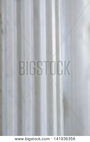 A close-up of an antique white marble fluted column