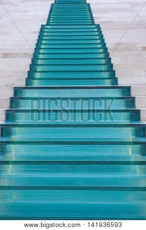 A modern blue glass and white marble staircase