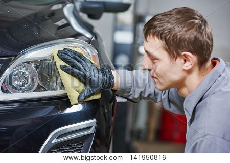 auto mechanic buffing and polishing car headlight