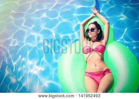 Portrait of a beautiful woman lying on air mattress in swimming pool