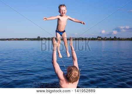 fun in the water. father throws up the kid up high standing in river. baby happy splash in the water. the concept of family lifestyle, summer vacation, water sport activities and fun leisure time with their parents.
