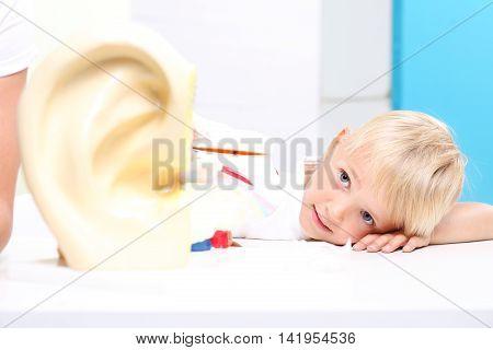 Children watch a model of the human ear.