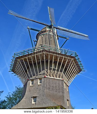 AMSTERDAM NETHERLANDS OCTOBER 01 2015: Nestled on the water at Zeeburgerdijk swings the huge blades of Amsterdam only windmill. But next door is the organic craft brew centre, Brouwerij 't IJ