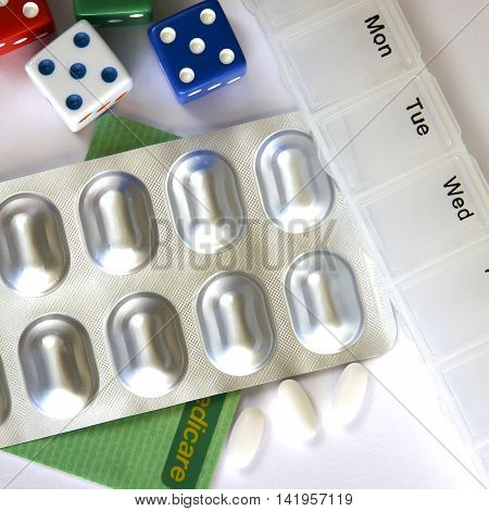 Pills, weekly pill box, dice and medicare card.