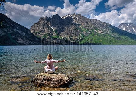 Woman meditating by water. Jenny Lake in Grand Tetons National Park Jackson Wyoming.