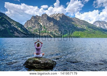 Woman in yoga pose meditating by lake. Jenny Lake in Grand Tetons National Park Jackson Wyoming.