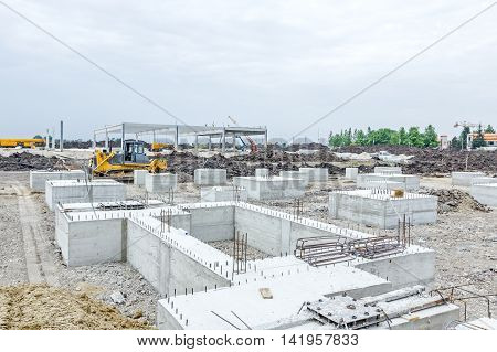 Concrete base of new edifice with reinforcement at building site is ready for next step.