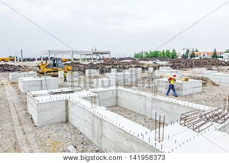 View on team of construction workers who are transfer mold components for assembling over building site.
