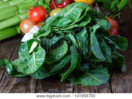 Bunch of mangold. Fresh mangold and vegetables on wooden rustic background