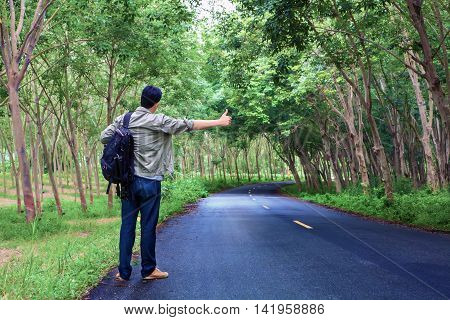 Hitchhiking Tourism Concept. Travel Hitchhiker Man Carrying Backpack Walking On The Road Passes Thro