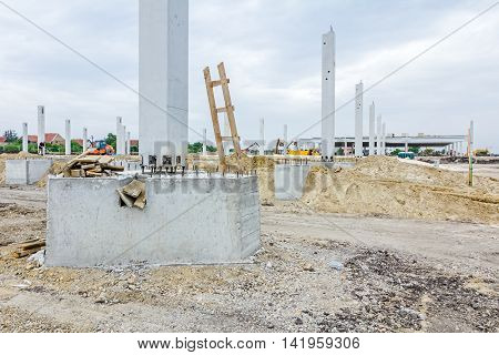 Workers are used wooden ladder at construction site. Reinforced steel bars are protruding from the concrete pillar base for new edifice.