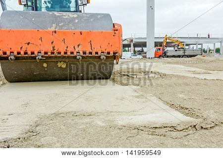 Steamroller is compacting sand among base pillars passing over. Landscape transform into urban area.