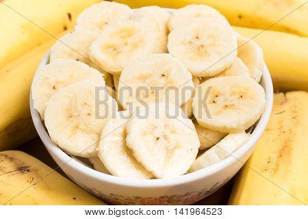 Prata Banana slices into a bowl over a wooden table