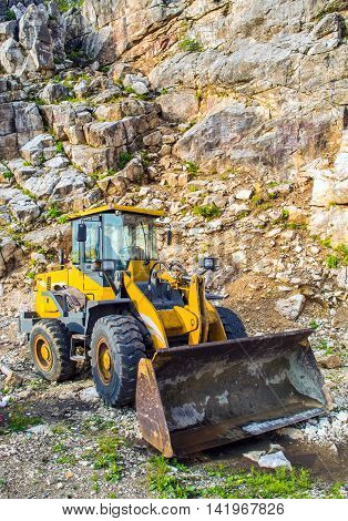 Yellow front end loader machine scooping up big stones in a quarry