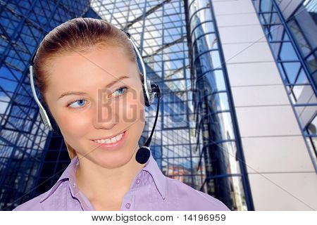 Woman wearing headset in office; could be receptionist on business architecture background