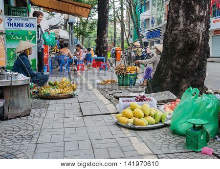 Ho Chi Minh City, Vietnam - October 12, 2013; Poverty forces people into street vending women wait for passing buyers with their trays of fruit in a Saigon Ho Chi Min City street Vietnam
