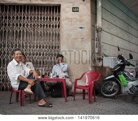 Ho Chi Minh City, Vietnam - October 12, 2013; Three Vietnamese happy smiling men taking a break sit at plastic table on plastic chairs with their drinks and cigarette packets on street corners in Vietnam Saigon Ho Chi Min City