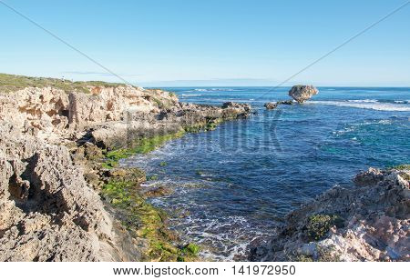 Rugged limestone bluffs with the Indian Ocean seascape and rocky outcroppings at Point Peron in Rockingham, Western Australia