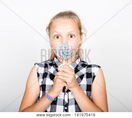 Portrait of happy beautiful young girl licking sweet candy and expressing different emotions. pretty teenager girl with big circle lollipop.