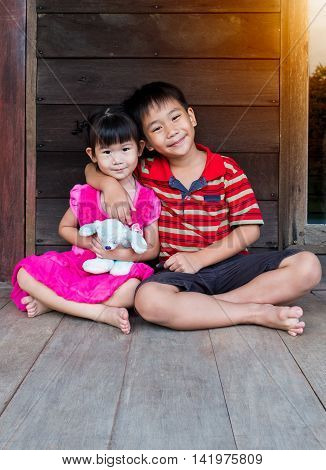 Asian Brother Put One's Arm Around Sister's Shoulder And Smiling Happy Together.