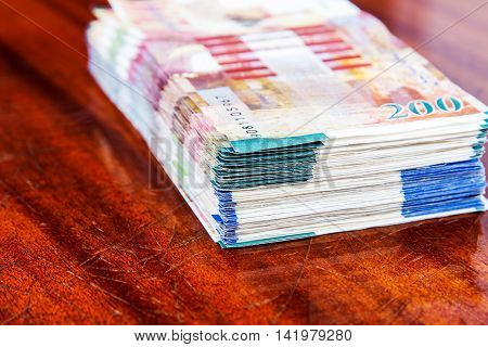 Two hundred and one hundred shekel bank notes against wood background. Concept photo of money banking currency and foreign exchange rates.