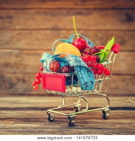 Shopping cart with fruits, berries and tape line on old wood background. Toned image.