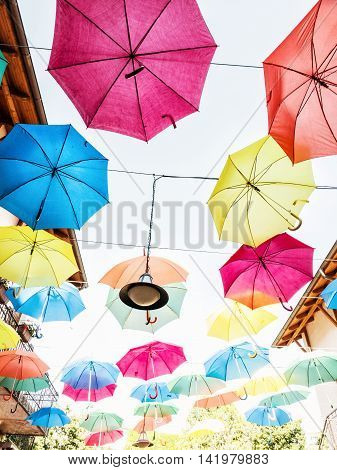 Bright colorful hanging umbrellas scene. Vertical composition. Vibrant colors. Holiday background. poster