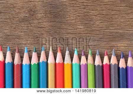 Closeup Color pencils concatenation on old wooden background for concept design of education.