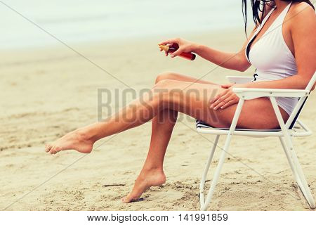 summer vacation, tourism, travel, holidays and people concept - close up of woman sunbathing in lounge and spraying sunscreen oil on beach