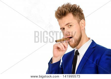 Handsome man smoking a cigar. Men's beauty, fashion. Isolated over white.