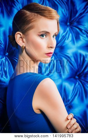 Gorgeous young woman in elegant evening dress standing by a vintage wallpaper. Fashion shot. Hairstyle.
