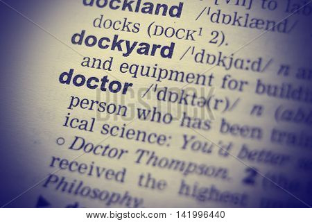 Close-up of word in English dictionary. Doctor definition and transcription