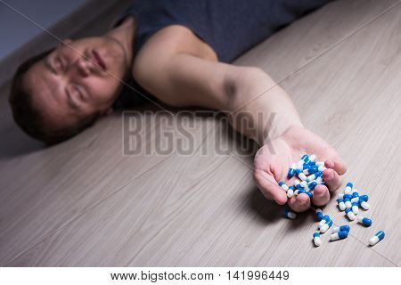 overdose or suicide - young stoned man with pills lying on the floor