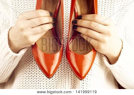 Fashion studio shot of shopping girl holding a red high heel shoe in her hand and looking at it. Isolated on white background. Professional makeup and hairstyle
